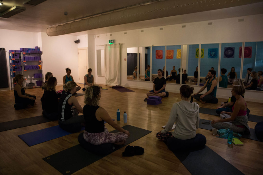 Students joined together in a circle at Yogafurie with the lights dimly lit