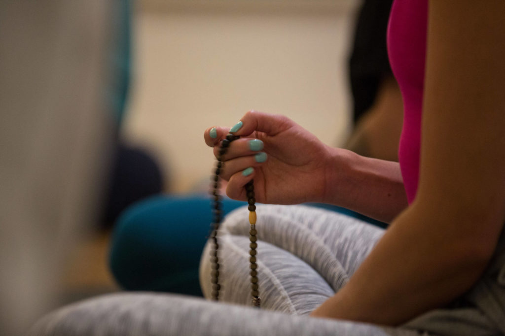 Person holding mala beads as they meditate