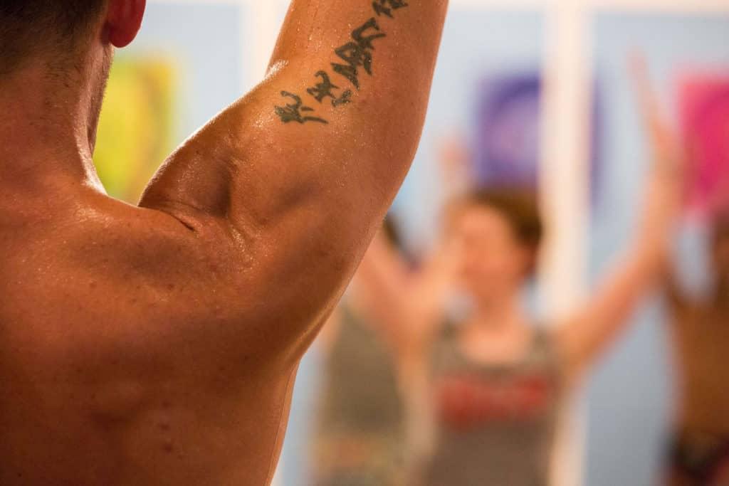Shot of man's shoulder in Hot Yoga class.
