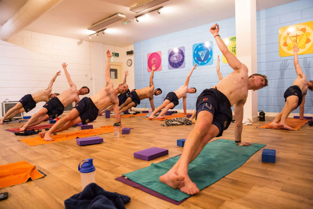 Cricket club class in Side Plank pose with both legs straight, left on top of right.