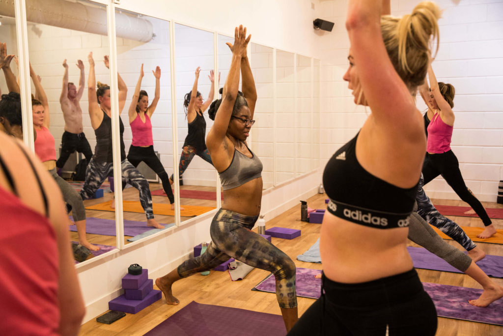 Class with Lemitra showing Warrior 3 pose with a view of the class in the mirrors.