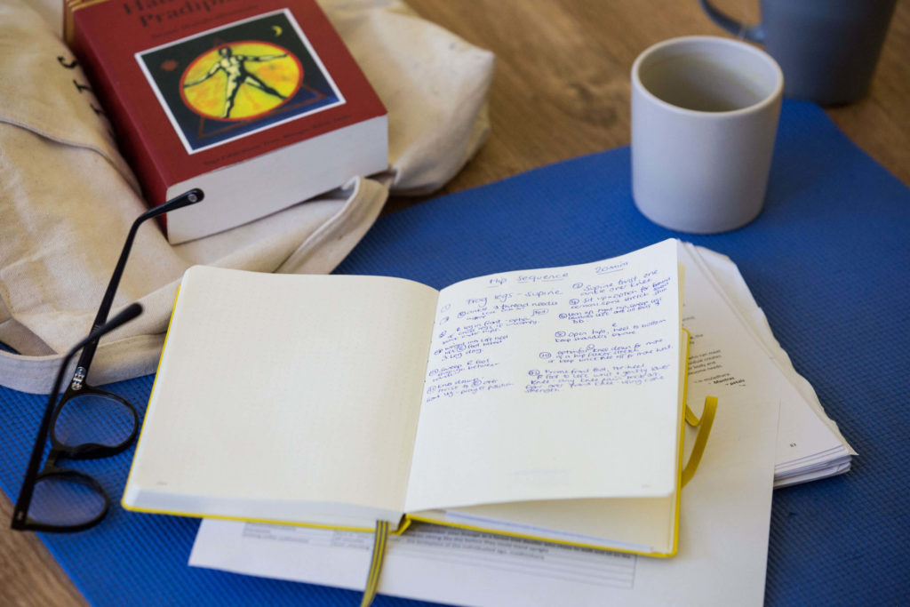 Studying in the studio - book of notes, coffee and yoga texbook.