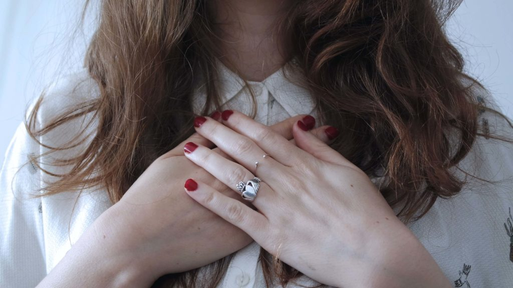 Woman holding her hands over her central chest area
