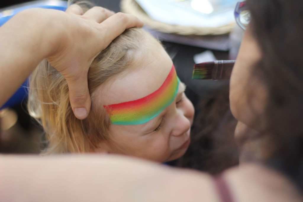 A child with a rainbow painted on their ajna third eye centre