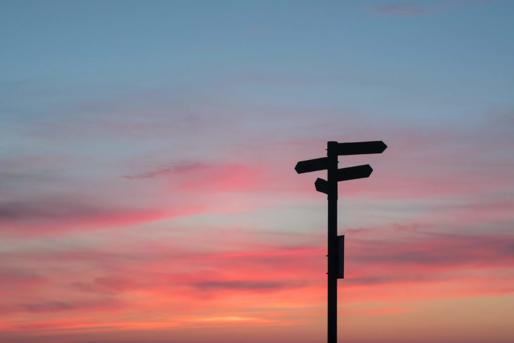 Photo by Javier Allegue Barros on Unsplash - Sunset behind a signpost, pointing to 4 different directions.