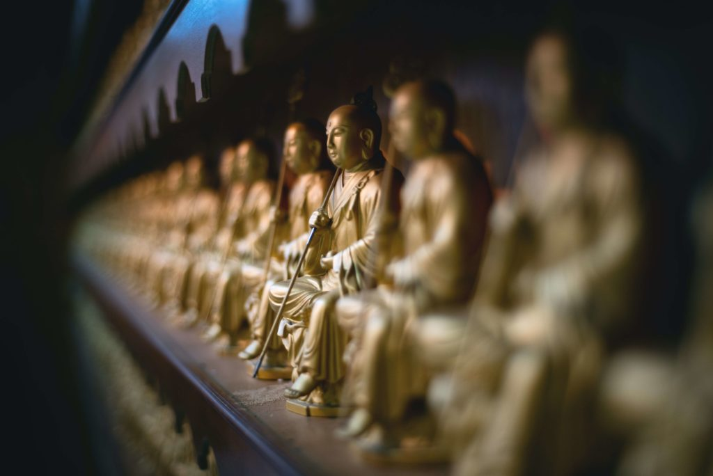 Mini statues of Buddha stacked on a shelf
