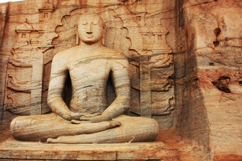 An image of Buddha carved into a stone wall