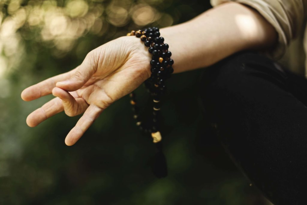 A demonstration of prithvi mudra with the tip of the ring finger brought to touch the tip of the thumb