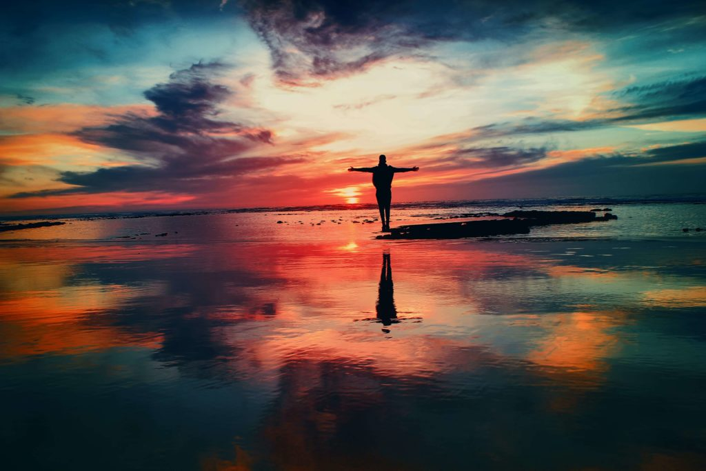 Photo by Mohamed Nohassi on Unsplash - Silhouetee standing on low tide beach at sunset.