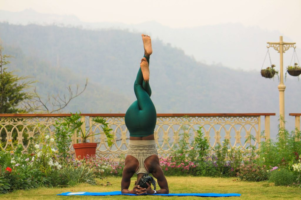 Woman practicing headstand with eagle pose legs