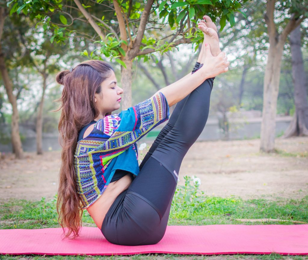 Ubhaya padanghustasana with the legs in boat outstretched and the hands on the feet