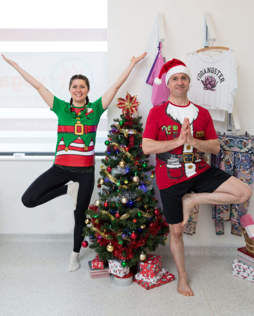 Ed and Sinead dressed festively, standing in tree pose by the Christmas tree.