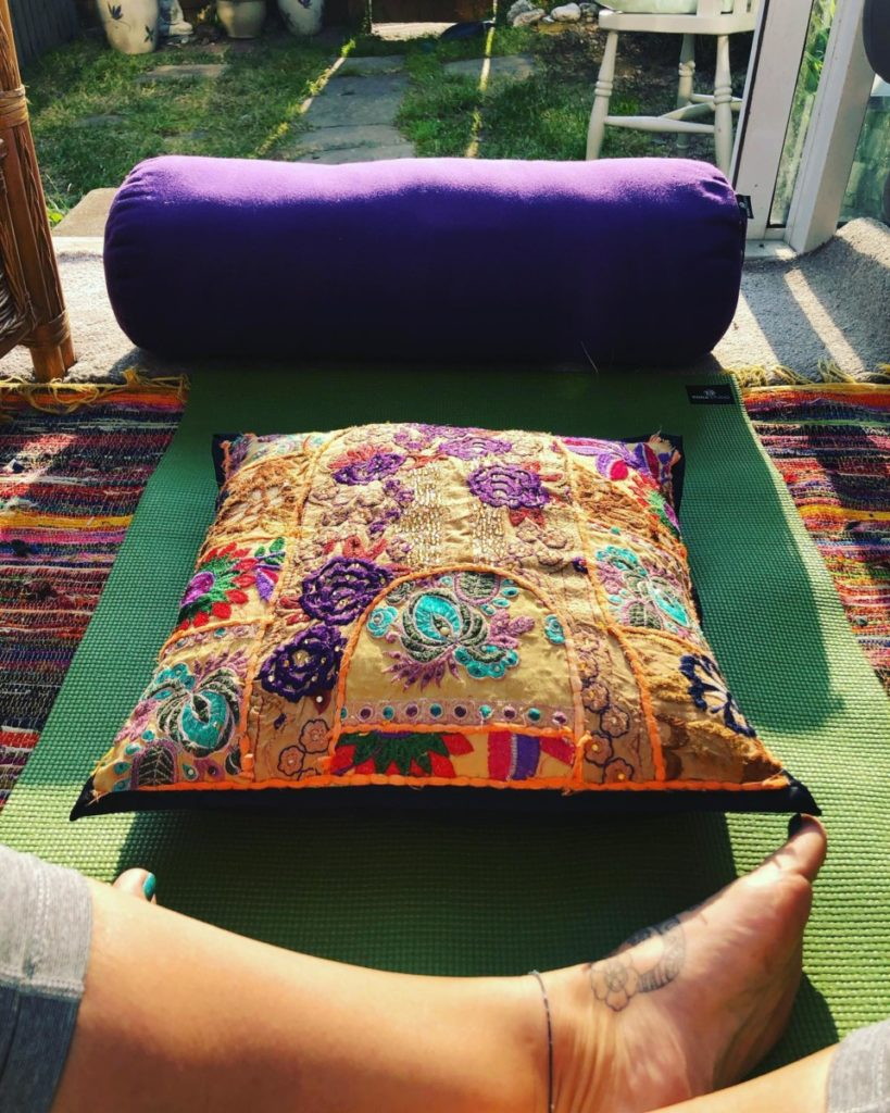 Photo from https://www.facebook.com/Yoga-with-Sian-252585672074422/photos/504311966901790 - Sian's mat and cushion set up for yoga in the sun.