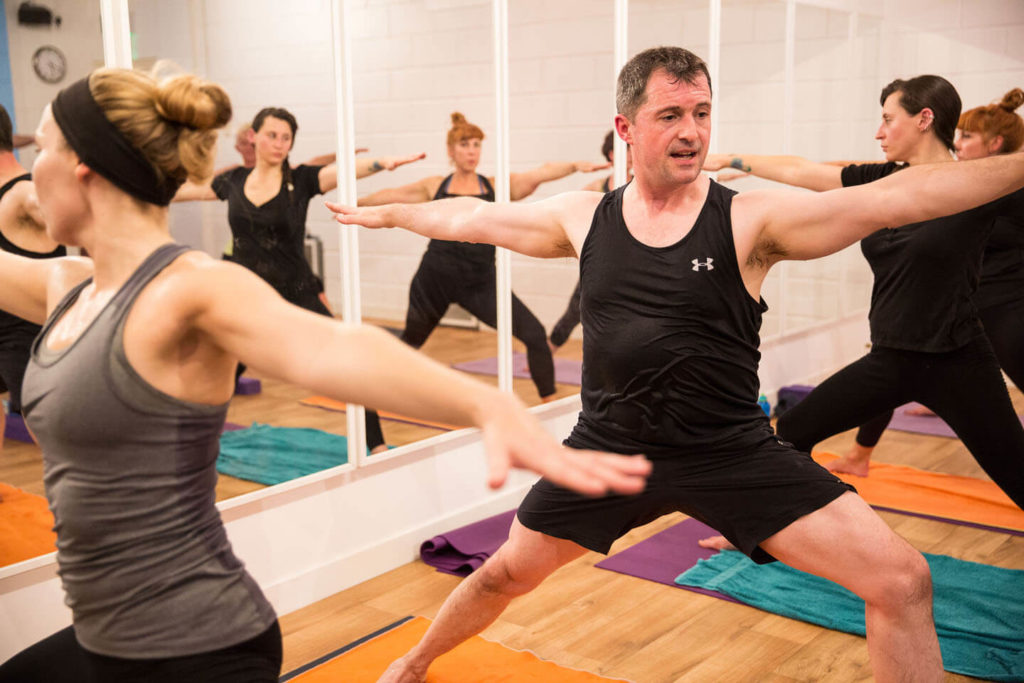 Hot yoga class with Ed - all in Warrior 2 pose.
