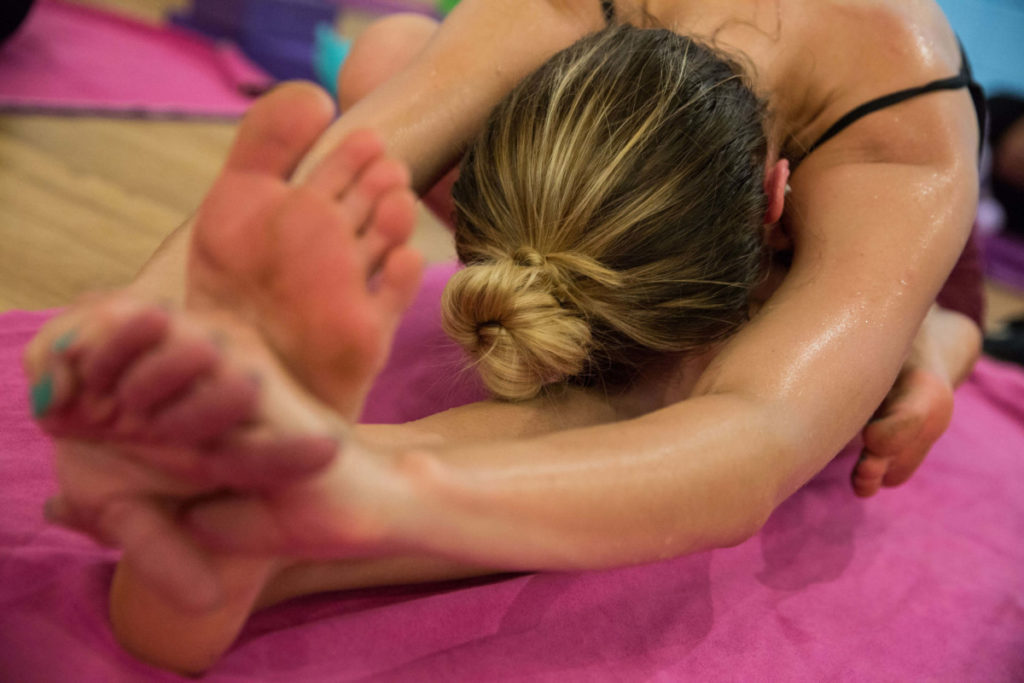Hot Yoga class member in seated position, body folded over straight leg, holding onto foot.