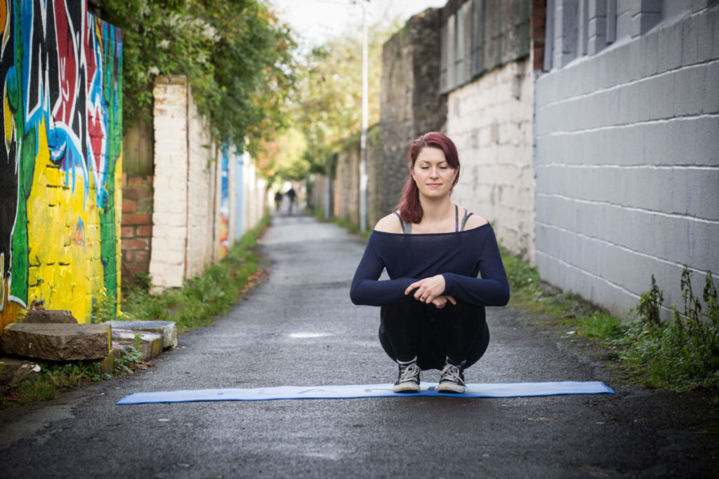 Sinead sitting crouched in the lane, eyes closed.