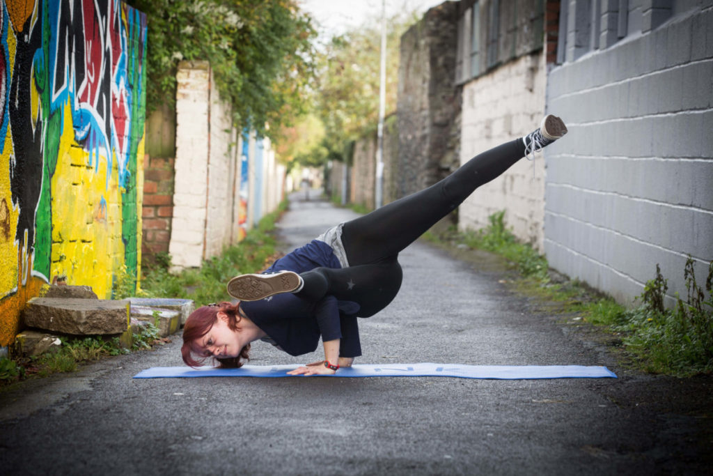 Sinead in arm balance in Happy Lane. Side crow pose with extended legs.