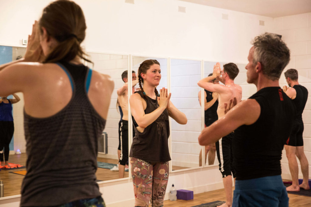 Sinead teaching Hot Yoga class, standing with hands at heart centre.
