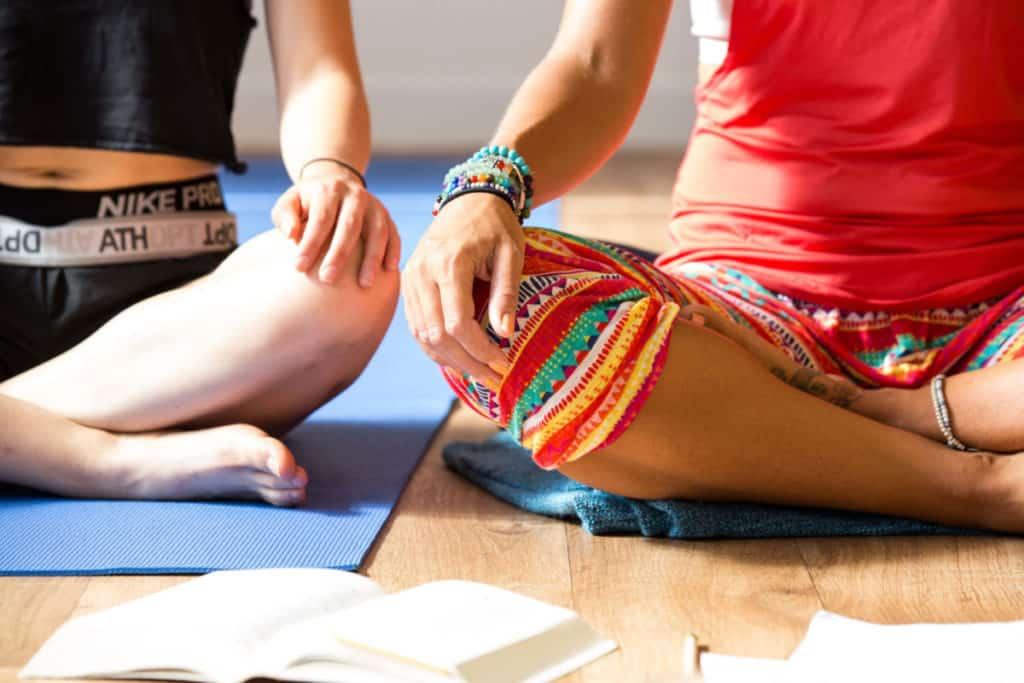 Teacher trainees sat cross-legged, hands resting on knees.