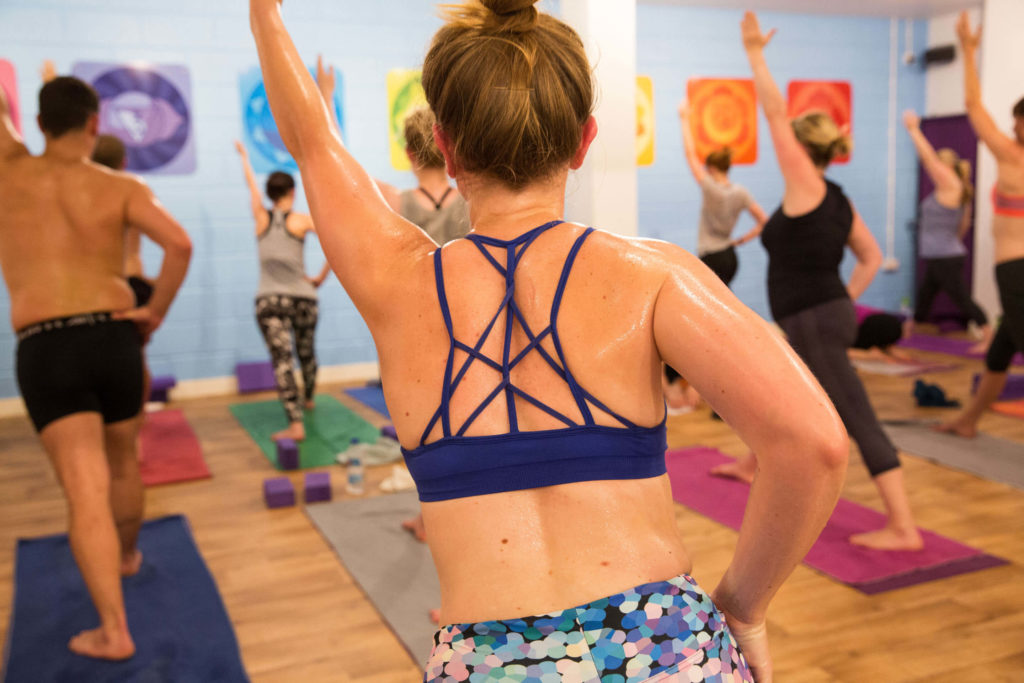 Teacher Trainee in Hot Yoga class in Warrior 1 pose but one hand on hip, one arm raised.