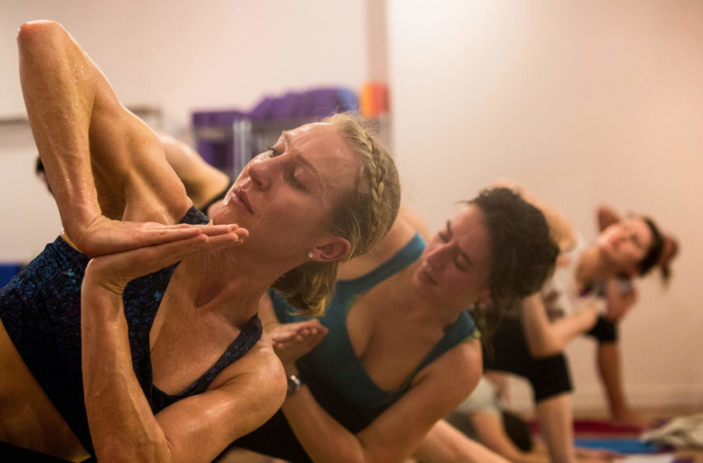 Hot Yoga class, members in twisted side angle, hands at heart centre.