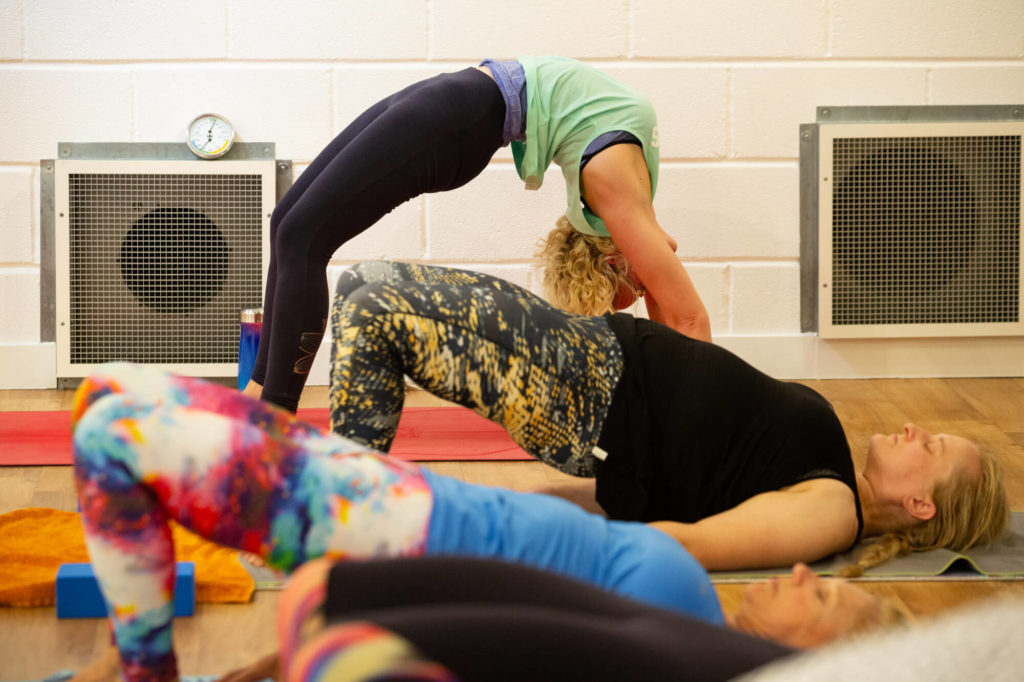Trainee teachers in different stages of bridge pose.