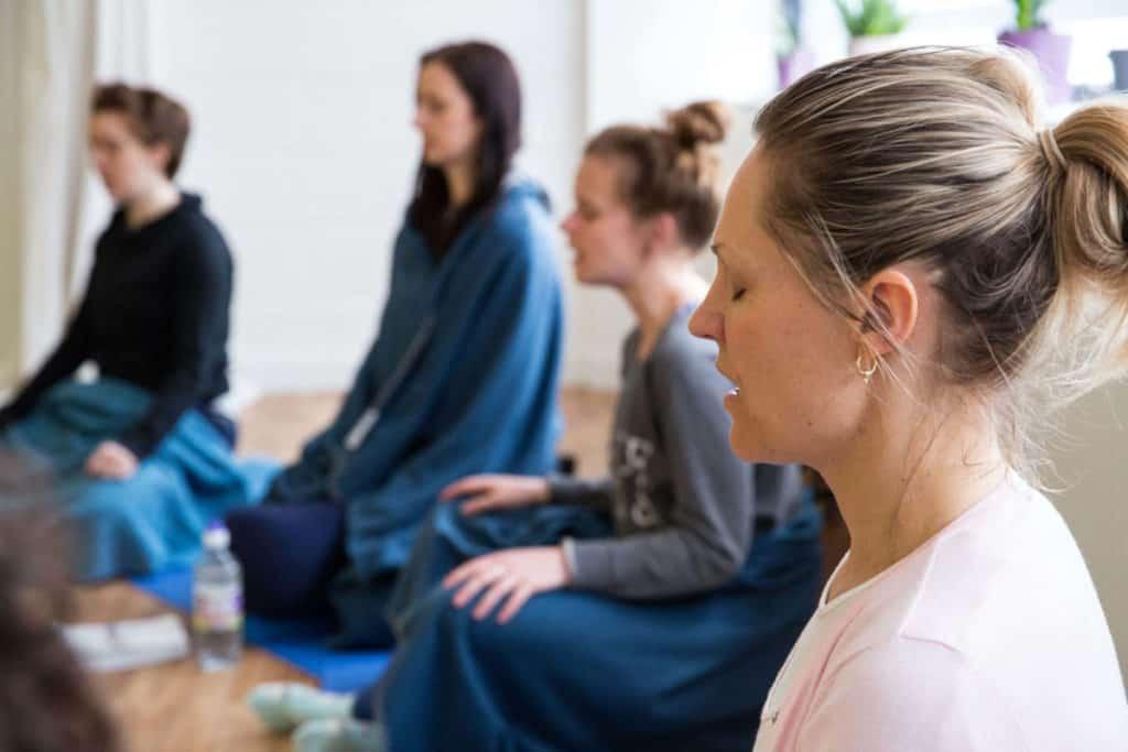 Teacher trainees sat in cirlce, practising meditation.
