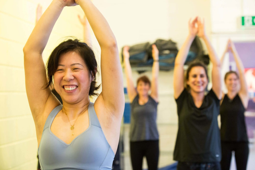 Yoga class standing with hands joined above the head, smiling.