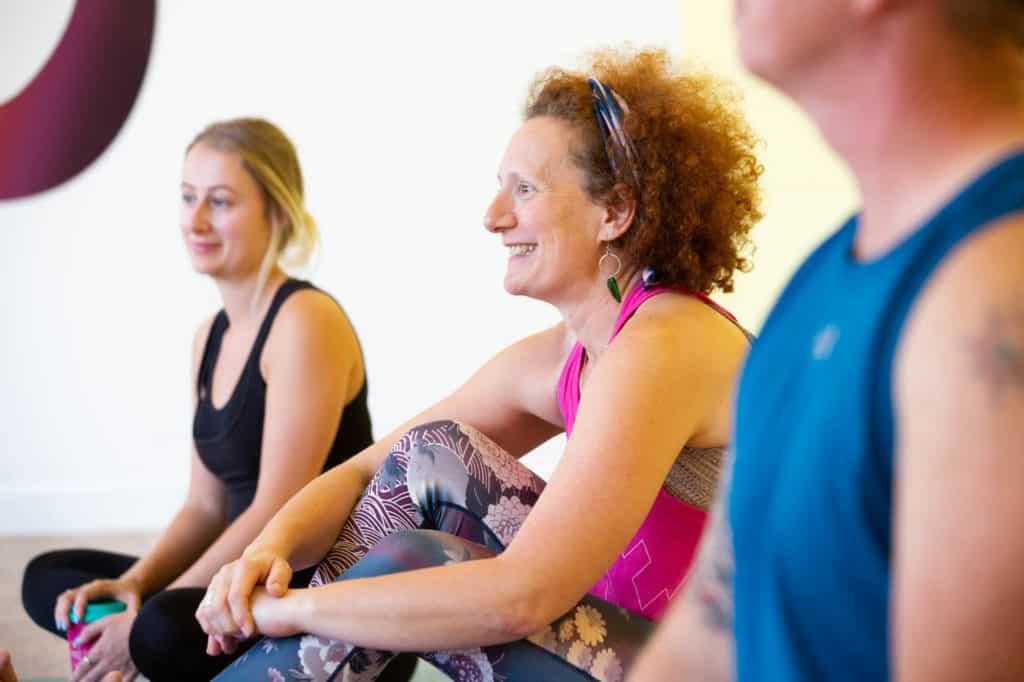 Teacher trainees sitting, chatting, smiling.