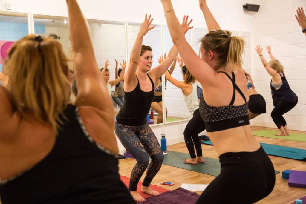 Sinead teaching Hot Yoga class in chair position.