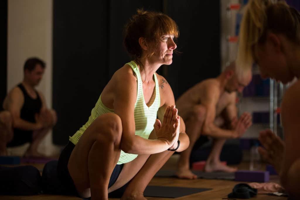 Yogafurie Teacher Trainee in Yogi squat in sunlight.