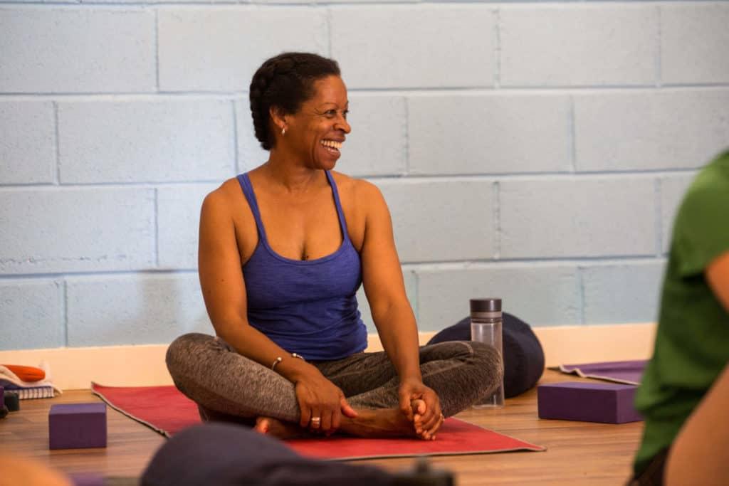 Smiling Teacher Trainee, sat cross-legged on mat.