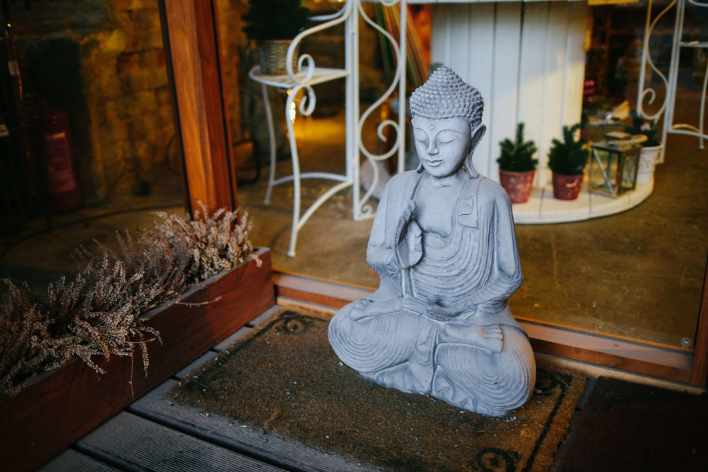 Buddha statuette on doormat. Photo by Anthony Fomin on Unsplash