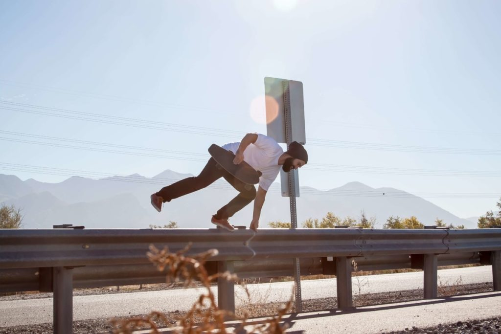 Man with skateboard jumping over barrier. Photo by Dillon Winspear on Unsplash