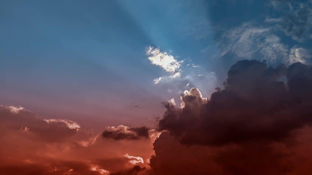 Clouds in the sky, blue above, red haze below. Photo by Emilian Zawrotny on Unsplash