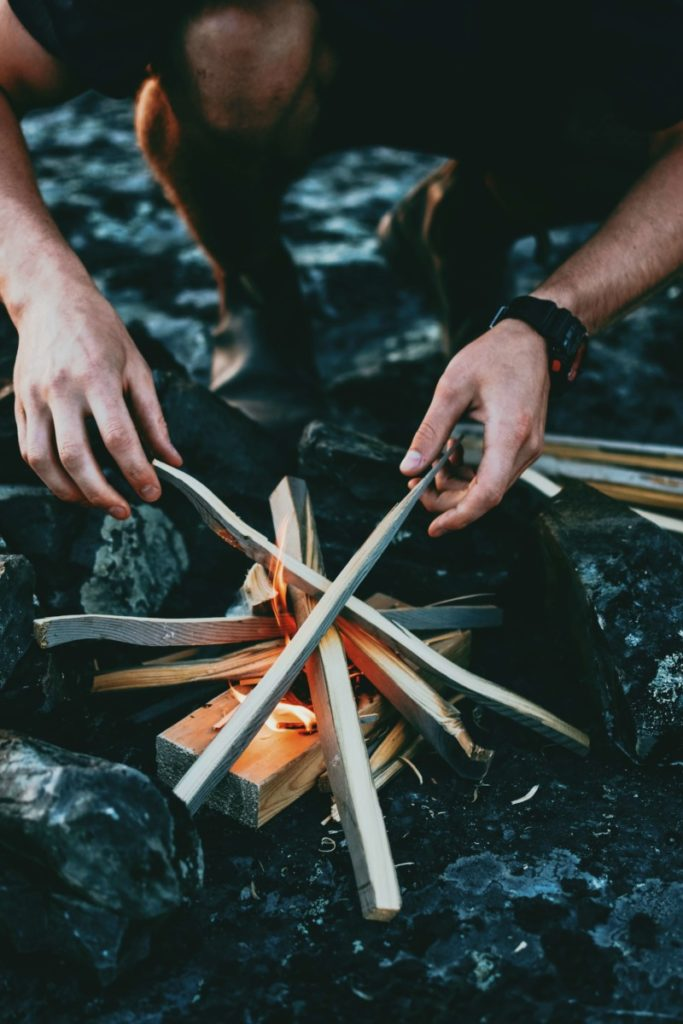 Man making fire out of kindling. Photo by Ian Keefe on Unsplash