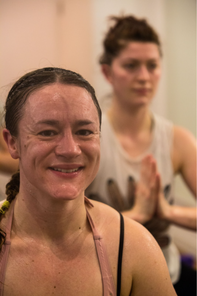 Amy Harrowell in hot yoga class, smiling.