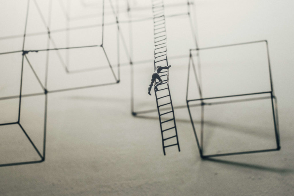 Figure man climing ladder among model scafolding of cubic structures. Photo by Jason Wong on Unsplash