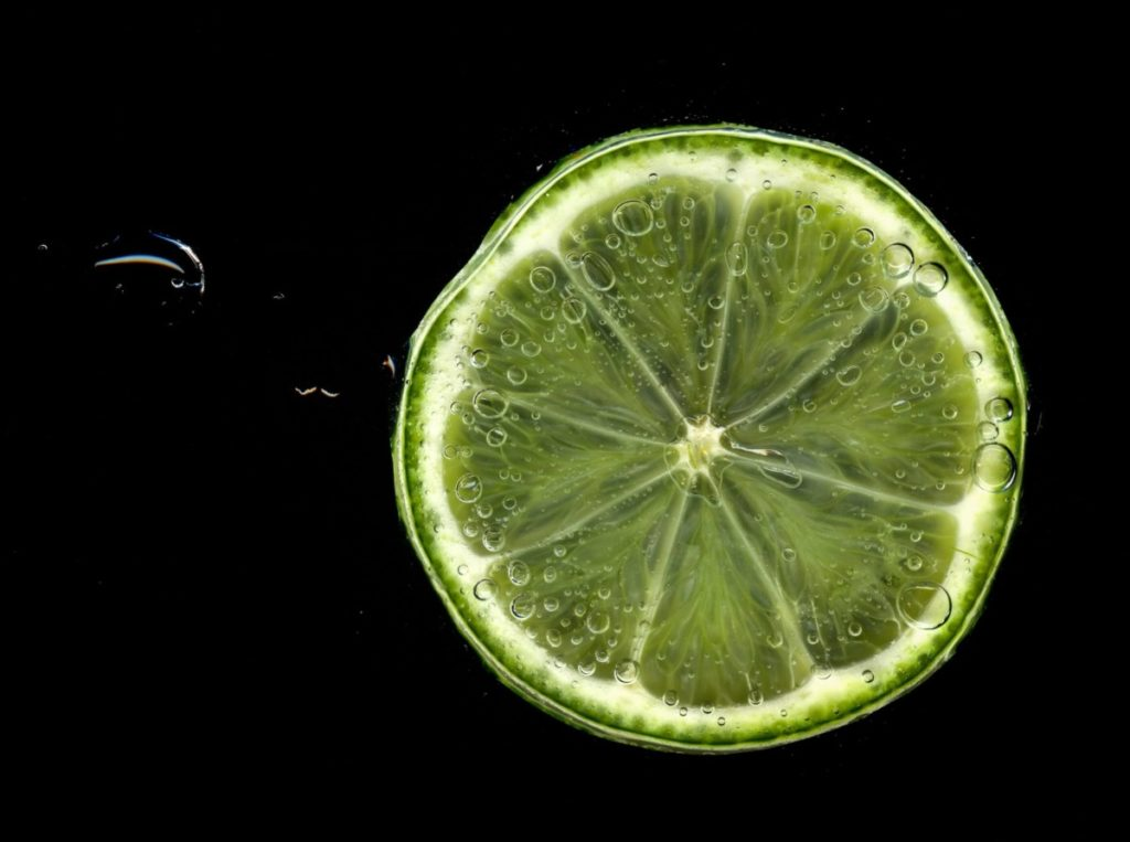 Bubbling lime slice on black background. Photo by Lesley Davidson on Unsplash