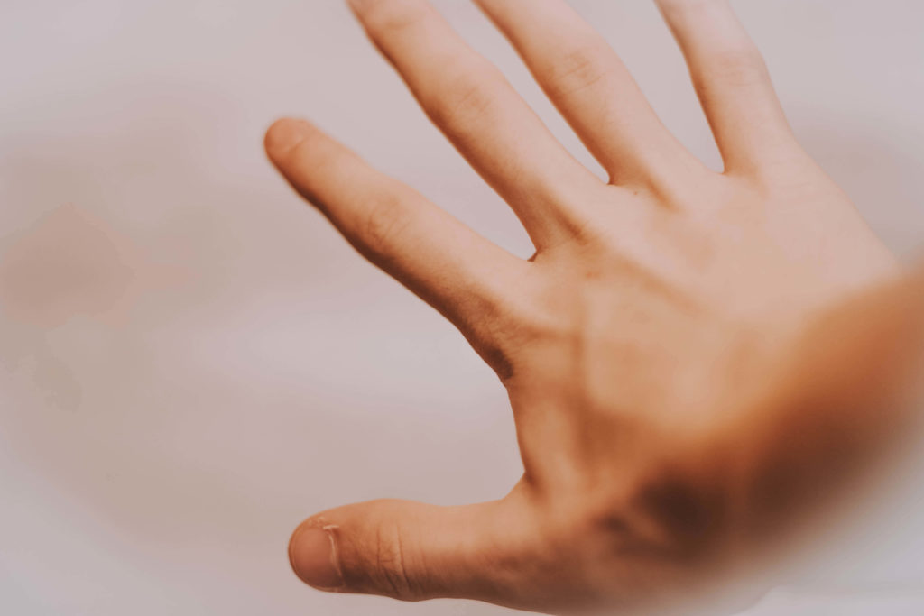Hand outstretched against blurred white background. Photo by Mat Reding on Unsplash