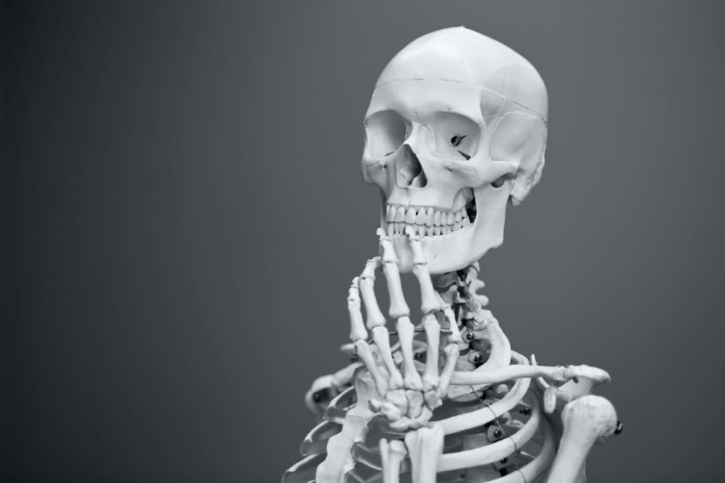 Skeleton holding hand to face in pensive manner.