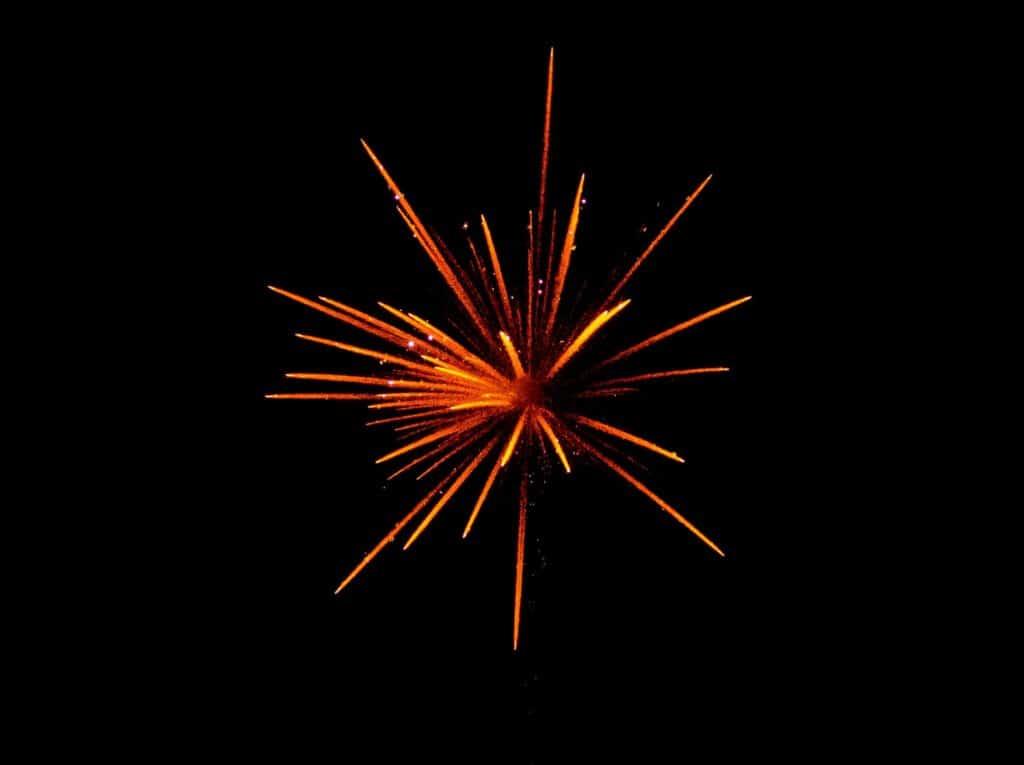 Orange firework against a black sky, Photo by Neenu Vimalkumar on Unsplash.