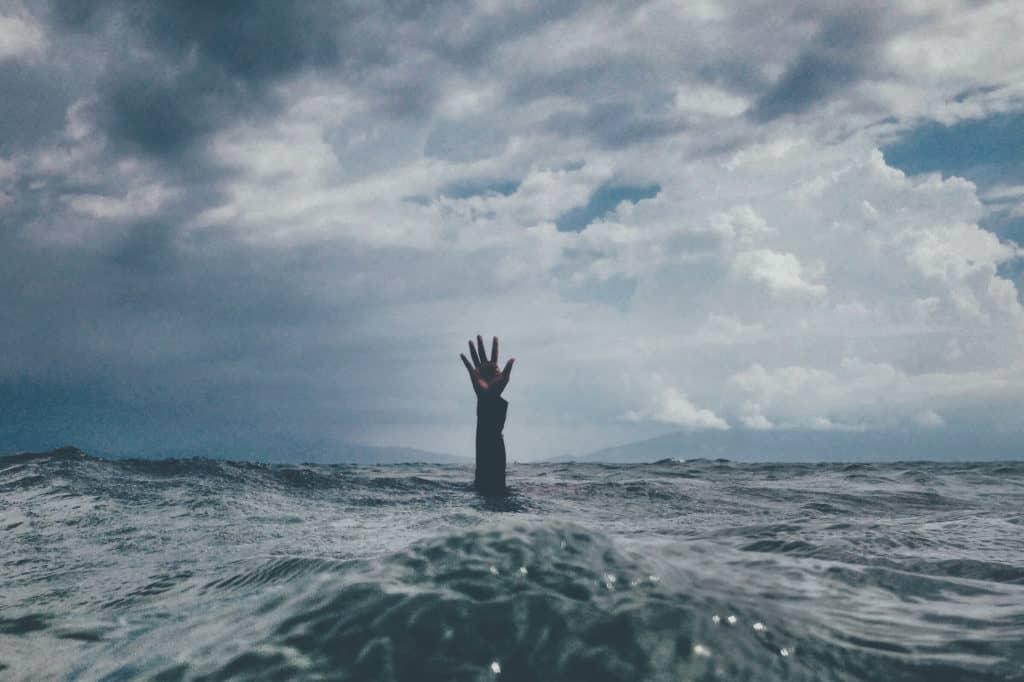 Hand reaching out of choppy ocean. Photo by nikko macaspac on Unsplash