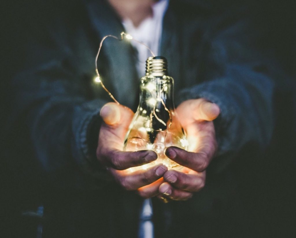 Man holding lightbulb filled with fairy lights. Photo by Riccardo Annandale on Unsplash