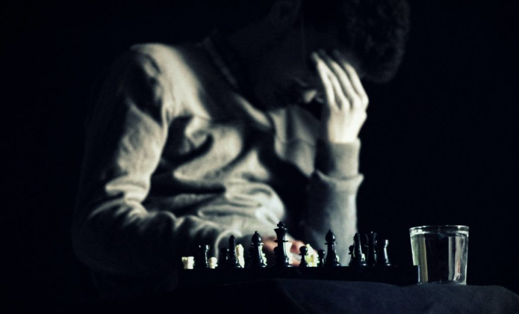 Chess board and player making hard decision. Photo by TAHA AJMI on Unsplash