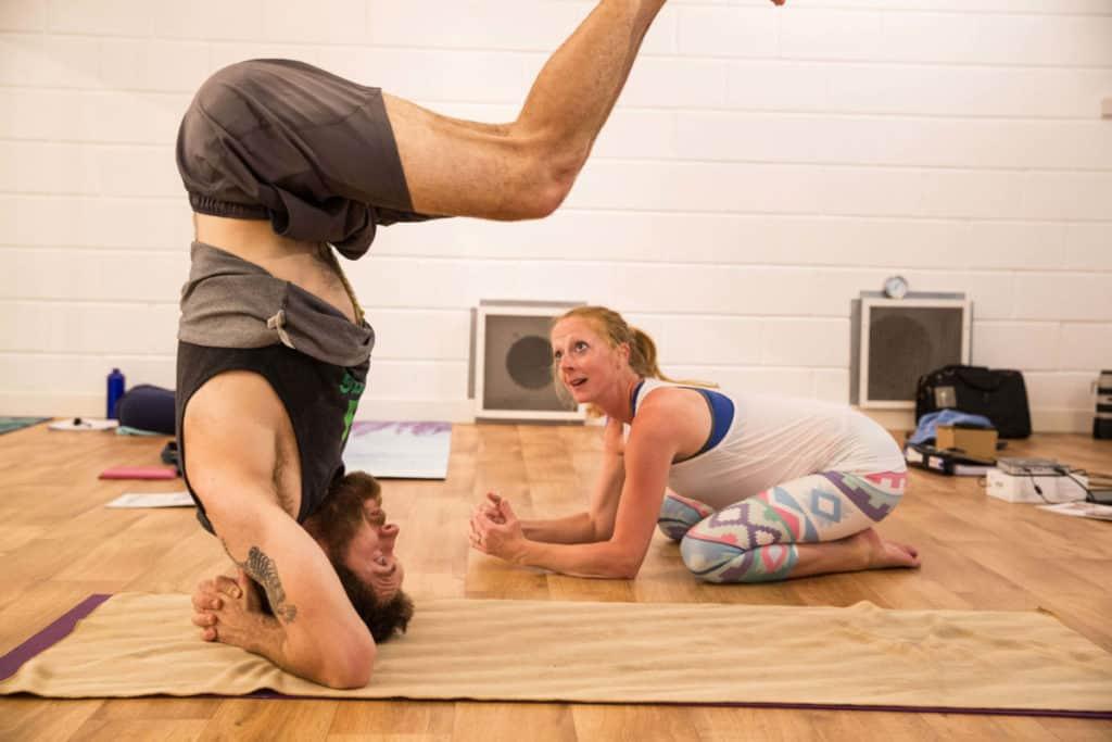 Teacher trainee assisting headstand balance.