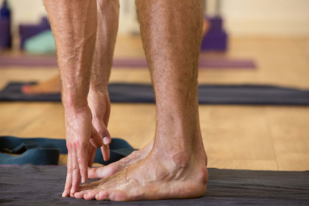 Hot Yoga class member touching toes.