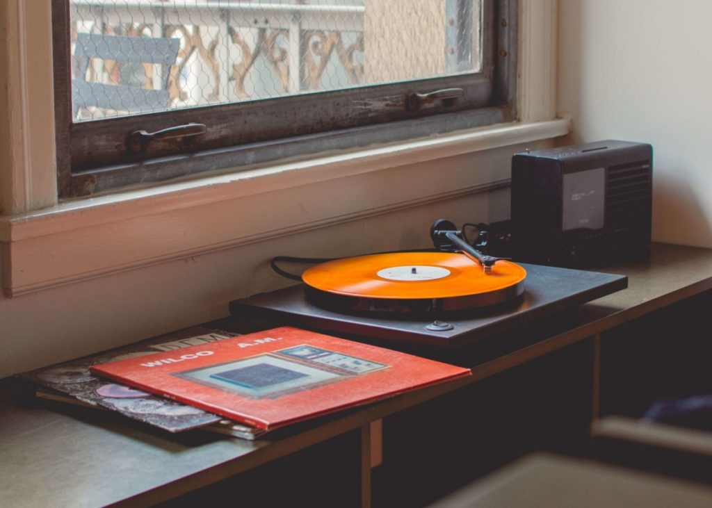 Record player playing records on a windowsill. Photo by Travis Yewell on Unsplash