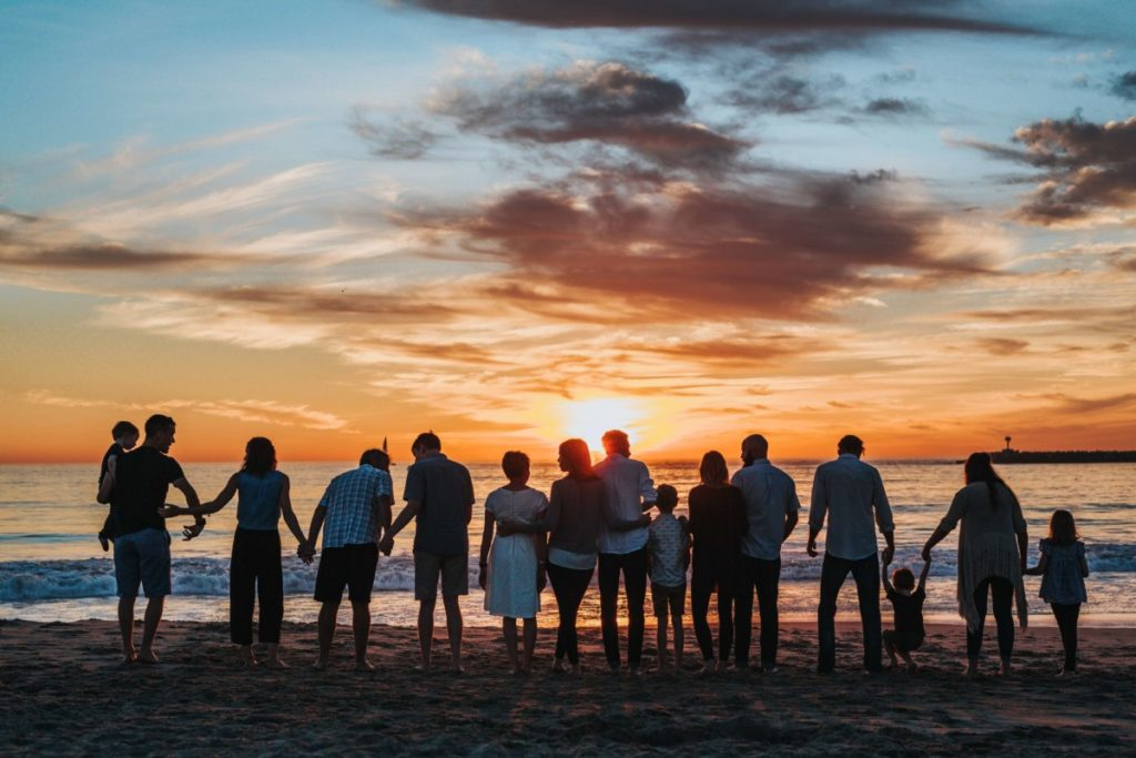 Large family lined up on beach at sunset. Photo by Tyler Nix on Unsplash