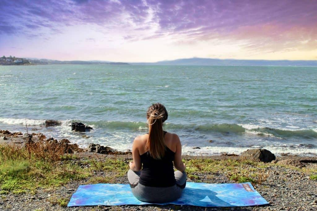 Woman sat on mat, facing the coast. Photo by Zen Bear Yoga on Unsplash